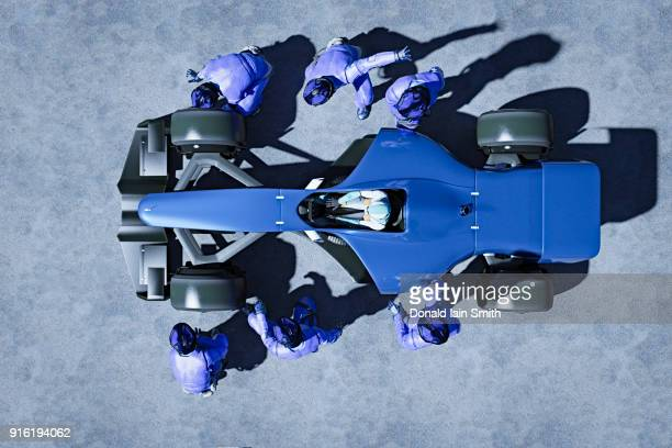 futuristic pit crew servicing race car - carro de corrida - fotografias e filmes do acervo