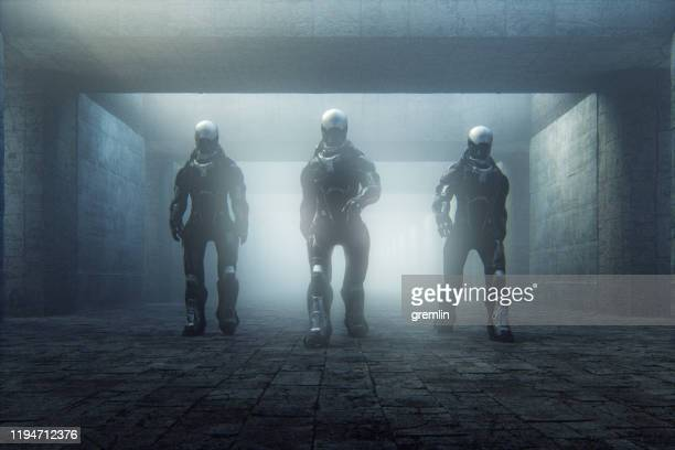 futuristic police cyborgs walking in old corridor - army soldier stock pictures, royalty-free photos & images
