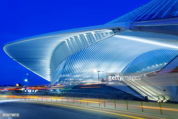 futuristic railway station building illuminated at night - belgië stockfoto's en -beelden