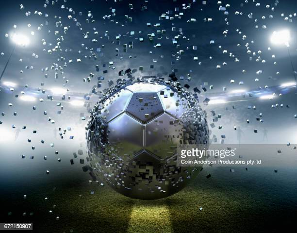 Futuristic silver soccer ball exploding into pixels