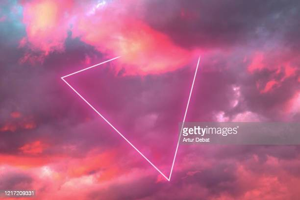 futuristic triangle neon in the burning sky with stunning pink colors. - triangle shape stock pictures, royalty-free photos & images