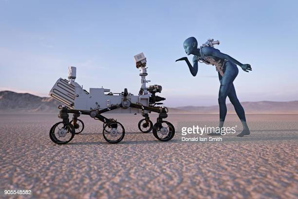 Futuristic woman blowing a kiss to robot in desert