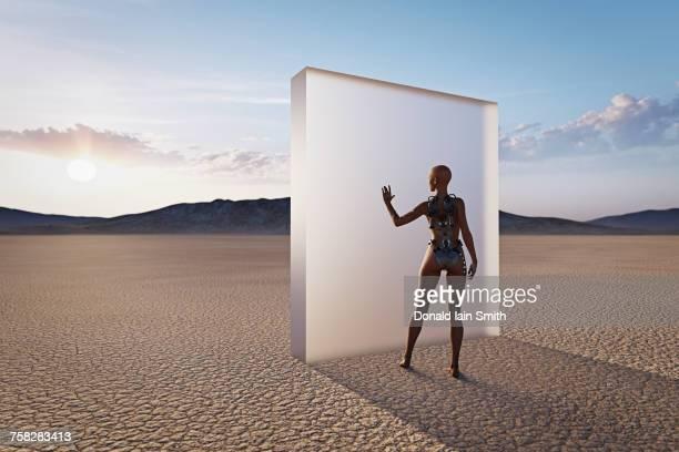 Futuristic woman touching glass wall in desert