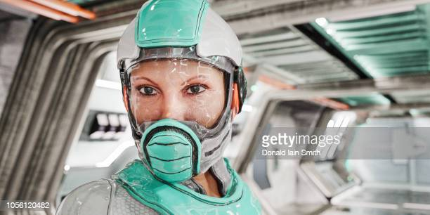 futuristic woman wearing space suit inside space ship corridor - space helmet stock photos and pictures