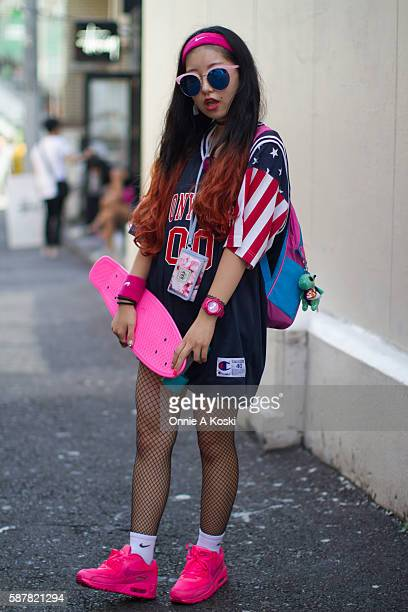 Fuuko Kitano carrying a pink skateboard is seen on Harajuku St wearing a Troll backpack a red white and blue vintage Champion basketball jersey black...