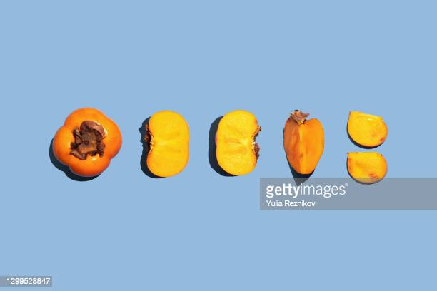 fuyu persimmons (khaki fruits) on the blue background - khaki stock pictures, royalty-free photos & images