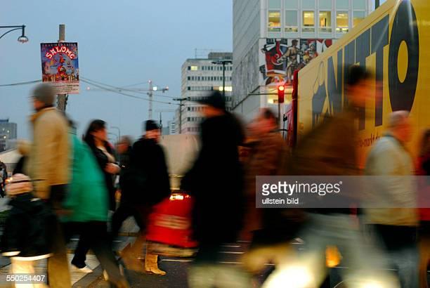 Fuzßgänger überqueren eilig eine Fahrbahn in Berlin-Mitte