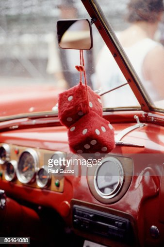 Fuzzy Dice Hanging In Rear View Mirror Of Car High-Res