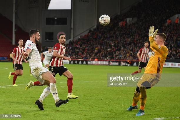 Fylde's English midfielder Jordan Williams chips the ball ofver Sheffield United's English goalkeeper Dean Henderson for their first goal during the...