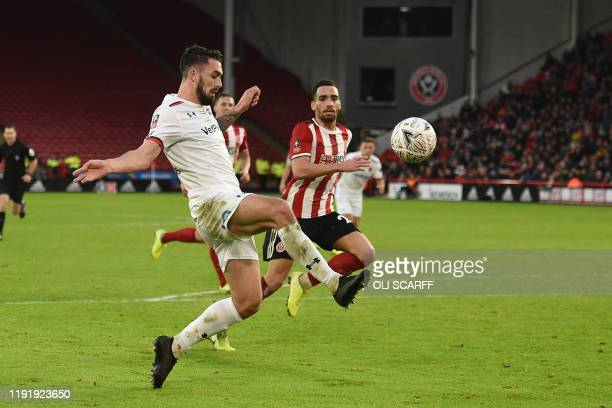 Fylde's English midfielder Jordan Williams chips the ball over Sheffield United's English goalkeeper Dean Henderson for their first goal during the...