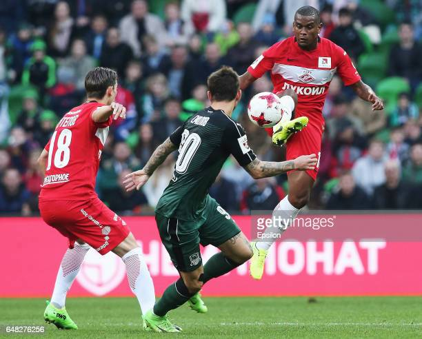 Fyodor Smolov of FC Krasnodar is challenged by Fernando and Ilya Kutepov of FC Spartak Moscow during the Russian Premier League match between FC...