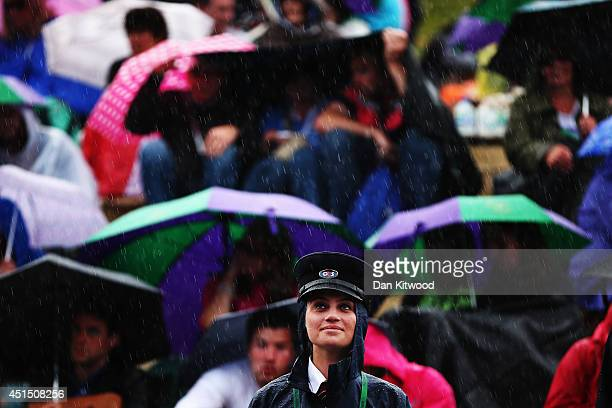 G4s Security out in the rain remain in good humor as fans sitting on Murray mound shelter under umbrellas as they watch the Andy Murray against Kevin...