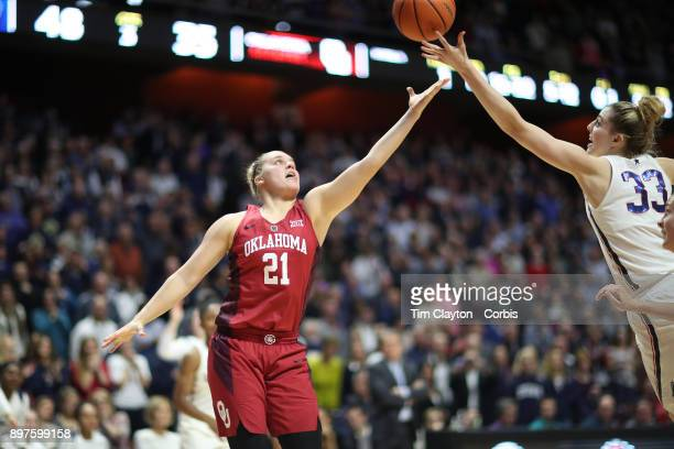 Gabbi Ortiz of the Oklahoma Sooners and Katie Lou Samuelson of the Connecticut Huskies challenge for a rebound during the Naismith Basketball Hall of...