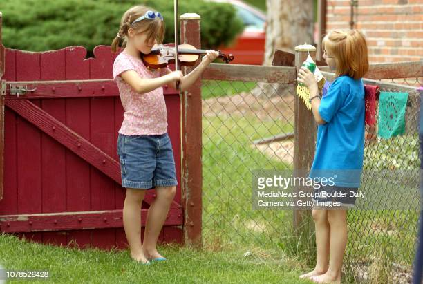 Gabby Diamond left polays her violin while her best firend Jolie Crowther watches before the Diamonds preform for friends at their Broomfield Heights...