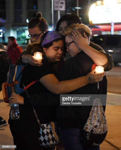 Gabby Phillips Sam Alworth Ana Preciado and Evan Dixon embrace during a vigil on the Las Vegas strip for the victims of the Route 91 Harvest country...