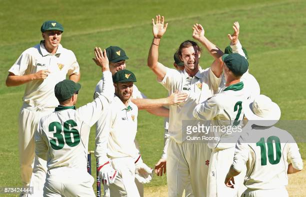 Gabe Bell of Tasmania is congratulated by team mates after getting the wicket of Peter Handscomb of Victoria during day one of the Sheffield Shield...
