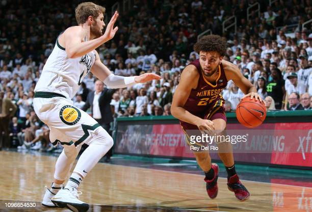 Gabe Kalscheur of the Minnesota Golden Gophers drives to the basket while defended by Kyle Ahrens of the Michigan State Spartans in the second half...