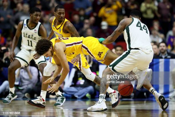 Gabe Kalscheur of the Minnesota Golden Gophers falls to the court against Nick Ward of the Michigan State Spartans during the second half in the...