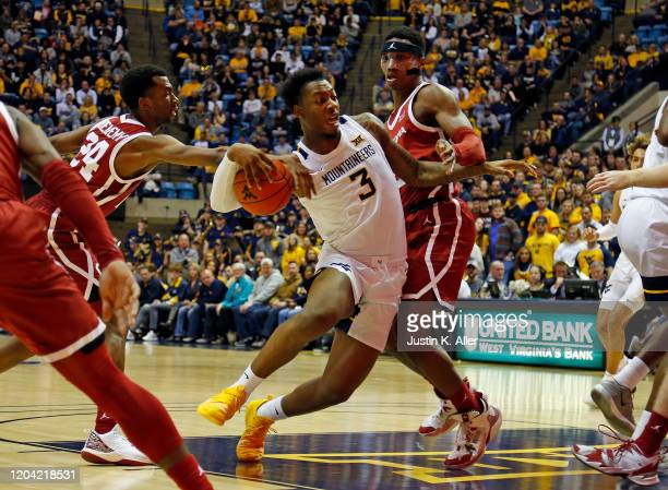 Gabe Osabuohien of the West Virginia Mountaineers drives the paint against Jamal Bieniemy of the Oklahoma Sooners at the WVU Coliseum on February 29...