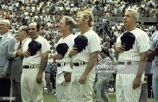 Gabe Paul Joe McCarthy Yogi Berra Whitey Ford Mickey Mantle and Joe Dimaggio of the New York Yankees hold their hats over their hearts as the...