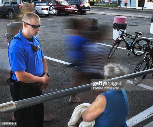 Groups of tourists steam past as York Police Reserve Officer Adam Schmidt questions a shoplifting suspect in downtown York August 11 2011