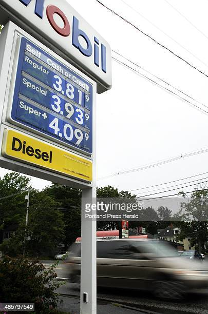 Photographed on Monday August 15 2011 Motorists zip past a Mobil station on Congress Street in Portland showing gas prices of $381 for regular 87...