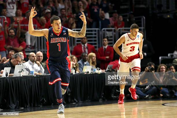 Gabe York of the Arizona Wildcats reacts after making a three-pointer alongside Zak Showalter of the Wisconsin Badgers in the first half during the...