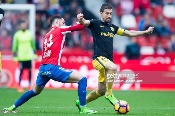 Gabi Fernandez of Atletico Madrid duels for the ball with Jorge Franco 'Burgui' of Real Sporting de Gijon during the La Liga match between Real...