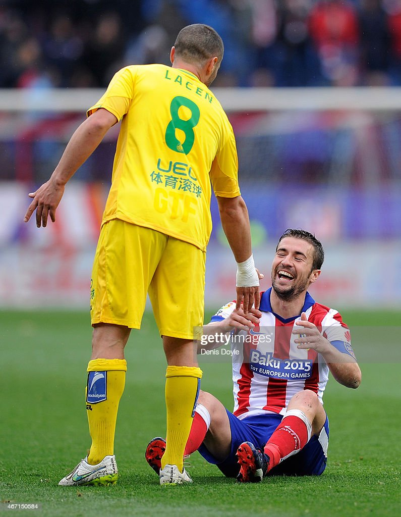 Gabi Fernandez of Club Atletico de Madrid is helped up by Medhi Lacen of Getafe CF during the La Liga match between Club Atletico de Madrid and Getafe CF at Vicente Calderon Stadium on March 21, 2015 in Madrid, Spain.