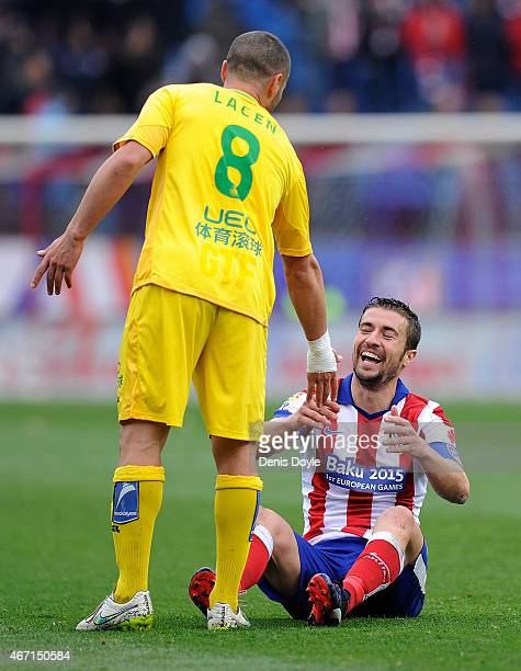 Gabi Fernandez of Club Atletico de Madrid is helped up by Medhi Lacen of Getafe CF during the La Liga match between Club Atletico de Madrid and...