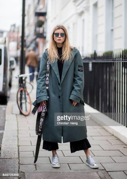 Gabija Varnaite wearing green coat flared cropped pants sneakers pink Alexandra Druzhinin bag during London Fashion Week September 2017 on September...