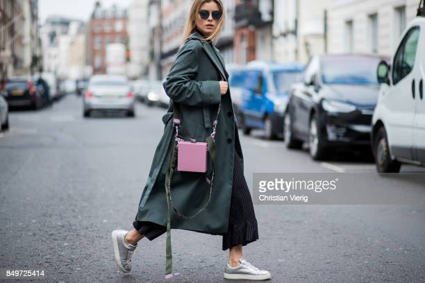 Gabija Varnaite wearing green coat, flared cropped pants, sneakers, pink Alexandra Druzhinin bag during London Fashion Week September 2017 on...
