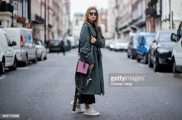 Gabija Varnaite wearing green coat flared cropped pants sneakers pink Alexandra Druzhinin bag during London Fashion Week September 2017 on September...