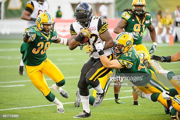 J Gable of the Hamilton TigerCats runs with the ball as Eric Samuels and JC Sherritt of the Edmonton Eskimos try to stop him during a CFL game at...