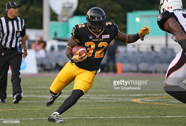 J Gable of the Hamilton TigerCats runs with the ball for an eventual touchdown during CFL game action against the Ottawa Redblacks on July 26 2014 at...