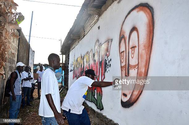 LEBUR Gabonese artist Regis Divassa and other street artists paint a graffiti reading 'Prohibited to urinate' on a wall of the Mebiame popular...