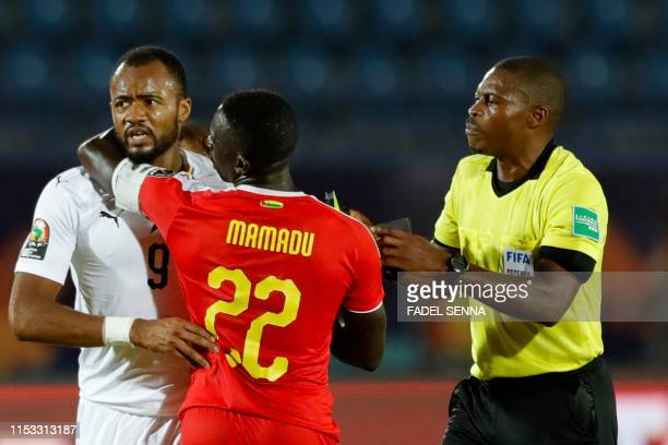 Gabonese referee Eric Castane separates Ghana's forward Jordan Ayew and Guinea-Bissau's defender Mamadu Cande during the 2019 Africa Cup of Nations...