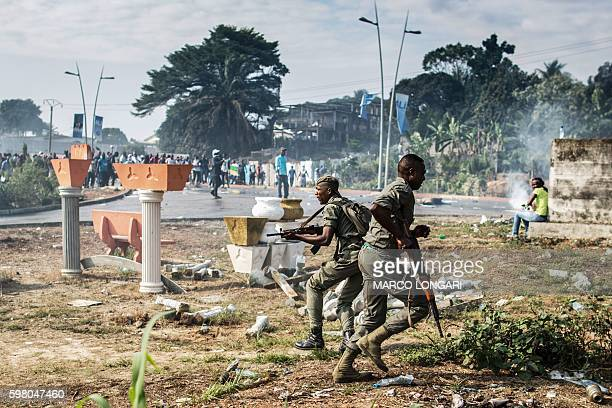 TOPSHOT Gabonese soldiers run to take position as supporters of opposition leader Jean Ping protest in front of security forces blocking a...