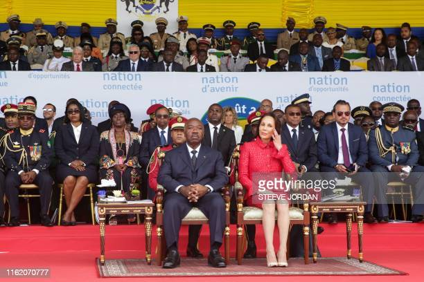 TOPSHOT Gabon's President Ali Bongo and his wife Sylvia Bongo sit on the tribune as they attend a parade during the country's independence day...