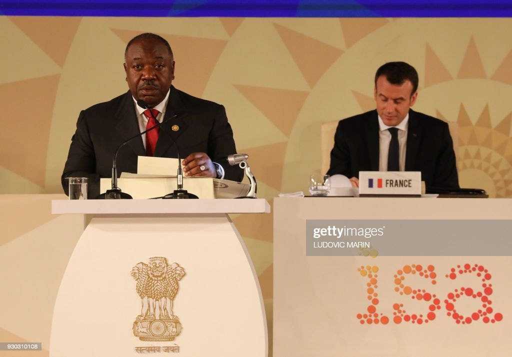 Gabon's President Ali Bongo delivers his speech next to French President Emmanuel Macron (L) and Indian Prime Minister Narendra Modi (C) during the founding conference of the International Solar Alliance in New Delhi on March 11, 2018. The International Solar Alliance (ISA) organizes more than 121 'sunshine' countries that are situated or have territory between the Tropic of Cancer and the Tropic of Capricorn, with the aim of boosting solar energy output in an effort to reduce global dependence on fossil fuels. / AFP PHOTO / Ludovic MARIN