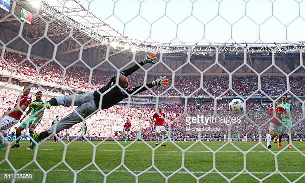 Gabor Kiraly of Hungary dives in vain as Cristiano Ronaldo of Portugal scores his team's second goal during the UEFA EURO 2016 Group F match between...