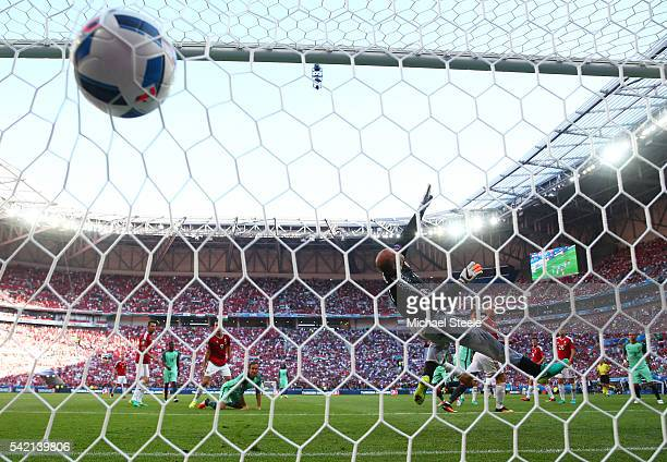 Gabor Kiraly of Hungary dives in vain as Cristiano Ronaldo of Portugal scores his team's third goal during the UEFA EURO 2016 Group F match between...
