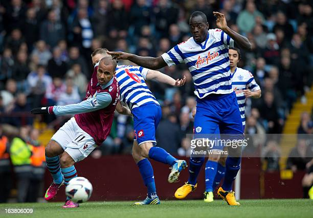 Gabriel Agbonlahor of Aston Villa is challenged by Chris Samba of Queens Park Rangers during the Barclays Premier League match between Aston Villa...