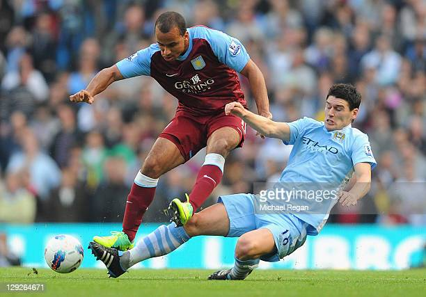 Gabriel Agbonlahor of Aston Villa is tackled by Gareth Barry of Manchester City during the Barclays Premier League match between Manchester City and...