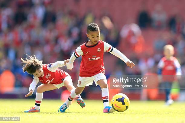 Gabriel Arteta son of Mikel and Elias Sagna son of Bacary play on the pitch after the game between Arsenal and West Bromwich Albion