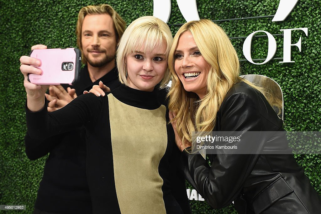 Gabriel Aubry (L) and Heidi Klum (R) pose with customers at the Glamour and INC International Concepts Denim Dash with Heidi Klum at Herald Square on October 30, 2015 in New York City.