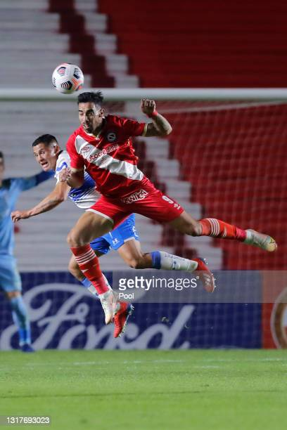 Gabriel Avalos of Argentinos Juniors and Marcelino Nuñez of Universidad Catolica jump for a header during a match between Argentinos Juniors and...