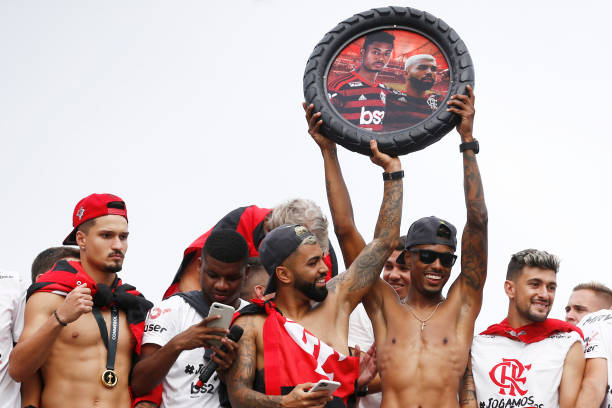 Gabriel Barbosa and Bruno Henrique of Flamengo hold up a picture form them on bus during the celebrations the day after Flamengo won the Copa...