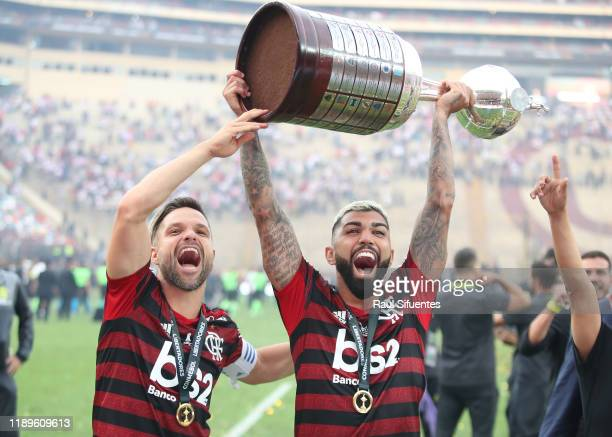 Gabriel Barbosa of Flamengo lifts the trophy with teammate Diego after winning the during the final match of Copa CONMEBOL Libertadores 2019 between...