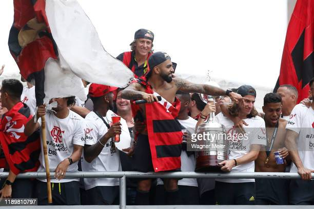 Gabriel Barbosa of Flamengo waves to fans as Filipe Luis holds the trophy on a bus during the celebrations the day after Flamengo won the Copa...